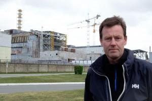 Nils Bøhmer med den falleferdige reaktor 4 i bakgrunnen. Bygningen begynte å slå sprekker for ti år siden, og deler av taket har allerede rast ned. Frykten er at tak eller vegger skal rase ned og treffe brenselet som fortsatt ligger der. Da vil radioaktivitet bli slynget opp i luften og bæres av sted med vær og vind.