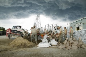 US Soldiers assigned to the Iowa Army National Guard construct a seven-foot levee to protect an electrical generator from rising floodwaters in Hills, Iowa
